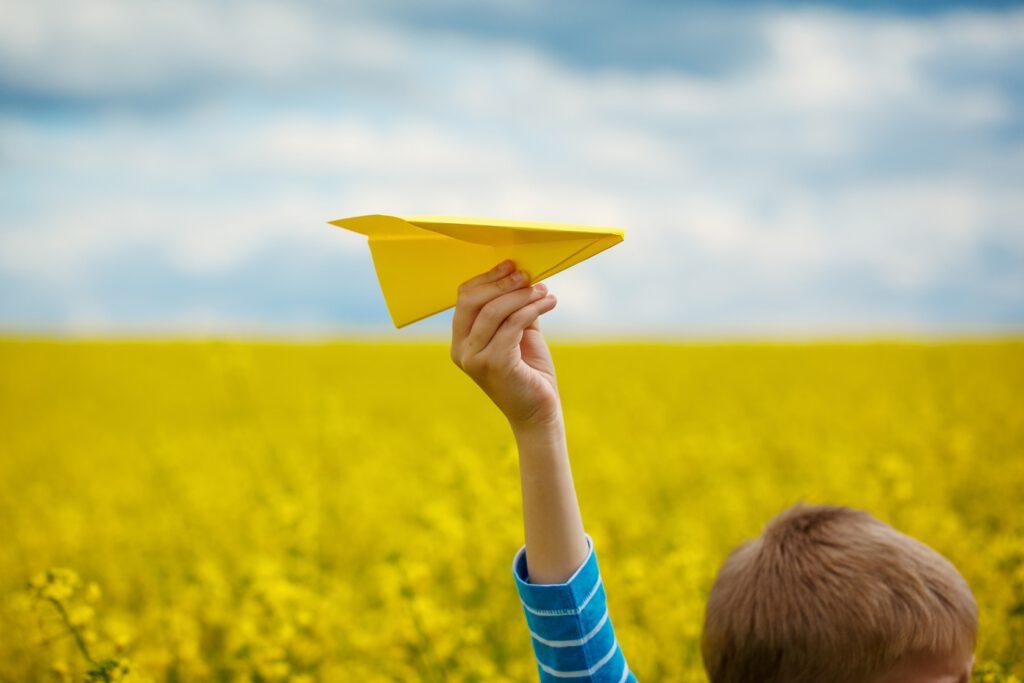 Mit einem Papierflieger spielendes Kind